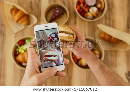 Food blogger reviewing takeout food, capturing video on his phone. Italian panini sandwich, french croissant with salmon & chocolate cheesecake. Close up, top view, pov, copy space, wooden background.