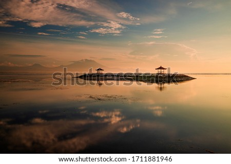 Sunrise landscape. Background with mountains and Agung volcano. Traditional gazebos on an artificial island in the ocean. Water reflection. Calm atmosphere. Soft focus. Sanur beach, Bali, Indonesia. #1711881946