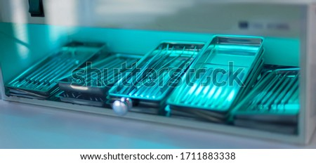 Sterilization of dentall instrument with ultraviolet lamp in dental clinic. Closeup different medical  instruments and accessories inside ultraviolt steriliser. Medical instruments sterilized under UV #1711883338