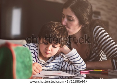Mother and son doing homework at home, kissing son Royalty-Free Stock Photo #1711885447