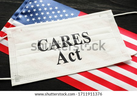 American flag and mask with sign cares act. Coronavirus Aid, Relief, and Economic Security law concept. Royalty-Free Stock Photo #1711911376