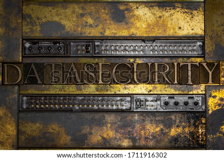 Photo of real authentic typeset letters forming Data Security text bordered by harddrive connectors on vintage textured grunge copper and gold background