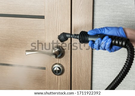 cleaning  door handle with steam generator, hand in blue glove holds steam genetator and hose with brush, which produces steam for disinfection from microbes, dirt and viruses, home cleaning concept #1711922392
