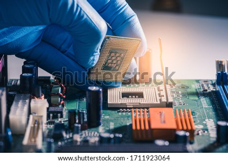 The technician is laying a CPU on the socket of the computer motherboard. the concept of computer, service, electronics, hardware, repairing, upgrade and technology. #1711923064