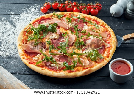 Baked pizza with salami, prosciutto and chicken with red sauce and melted cheese on a black wooden background in a composition with ingredients. Top view #1711942921