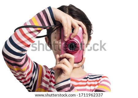 horizontal photo of a child isolated on a white background taking pictures with her pink camera, concept of kids and their hobbies