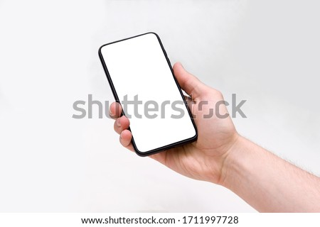 Man holding smartphone with blank screen on white background, closeup of hand. Space for text Royalty-Free Stock Photo #1711997728