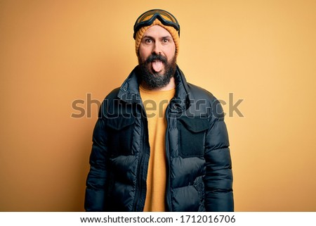 Handsome skier bald man with beard skiing wearing snow sportswear and ski goggles sticking tongue out happy with funny expression. Emotion concept. #1712016706