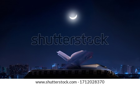 Quran, the islamic holy book, in dark  city background Royalty-Free Stock Photo #1712028370