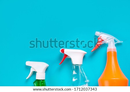 three spray bottles with cleaning agent on a blue background #1712037343