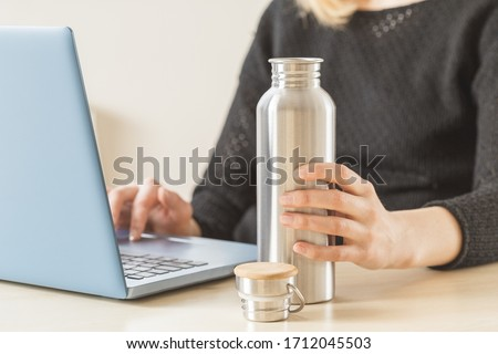 White woman holding her personal stainless steel water bottle on the working table. Daily hydration habit to stay healthy Royalty-Free Stock Photo #1712045503