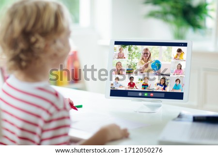 Online remote learning. School kids with computer having video conference chat with teacher and class group. Child studying from home. Homeschooling during quarantine and coronavirus outbreak. #1712050276