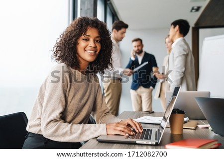 Attractive african young confident businesswoman sitting at the office table with group of colleagues in the background, working on laptop computer Royalty-Free Stock Photo #1712082700