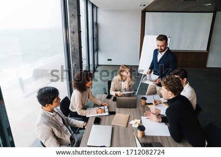 Group of smart multiethnic motivated businesspeople working together on a new project while sitting at the table in the office #1712082724