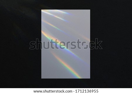 Empty white vertical rectangle a4 poster, business card, flyer mockup with overlay of rainbow light refraction caustic effect and shadow on trendy dark concrete background.