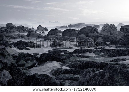 Rocky beach at dusk. Long exposure. Northern portuguese rocky coast. Converted black and white. Toned blue.