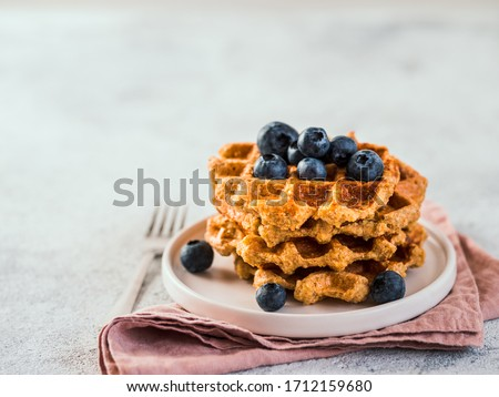 Easy healthy gluten free oat waffles with copy space. Stack of appetizing homemade waffles with oat flour decorated blueberries, on plate over light gray cement background #1712159680
