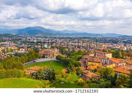 Aerial view of Bergamo city, Lombardy, Italy. Bergamo Alps (Alpi Orobie) begin immediately north of the city, on the background. Picturesque autumn view Royalty-Free Stock Photo #1712162185