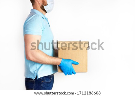Concept of delivery of goods during quarantine 2019-ncov. Young man with beard in medical mask and blue gloves holds cardboard box in his hands on white background. Contactless delivery virus protect #1712186608