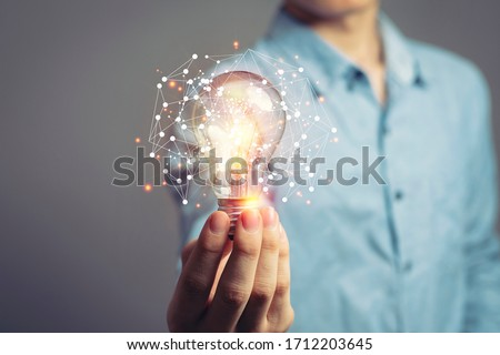 Man holding light bulbs, ideas of new ideas with innovative technology and creativity. concept creativity with bulbs that shine glitter. #1712203645