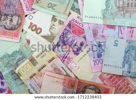 Different Ukrainian hryvnias for the background. A lot of money on black. #1712238403