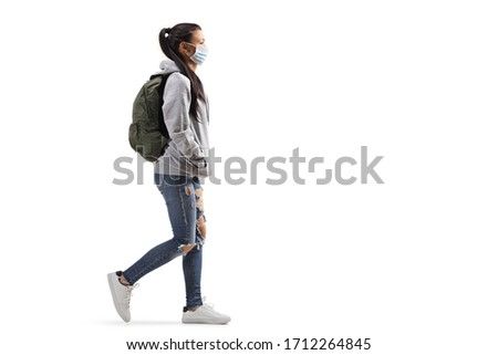 Full length profile shot of a casual female student wearing a protective medical mask and walking isolated on white background #1712264845