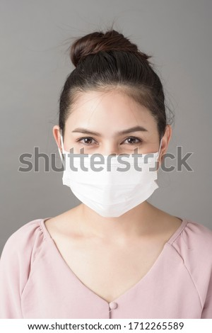 close up woman face is wearing surgical mask  #1712265589