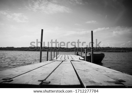 A black and white filtered boat dock pictures on a bright summers day. Still, glistening water enlightens the picture and fills it with glorious beauty!
