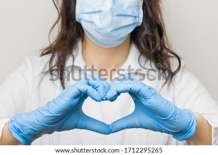 Stop SARSCoV, virus 2020, chinese virus COVID-19. Womens hand in blue medical gloves show heart sign. Concept of protection against HIV. Doctor in blue medical gloves and protective mask. #1712295265