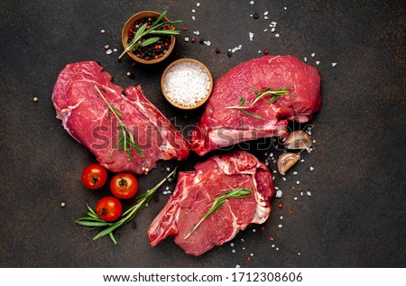raw three beef steaks on a cutting board with spices on a stone background #1712308606