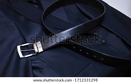 A black leather belt with steel fittings lies horizontally on a black men's jacket. An expensive gift option for men, premium leather, chic performance, handmade, exclusive. craft Royalty-Free Stock Photo #1712331298