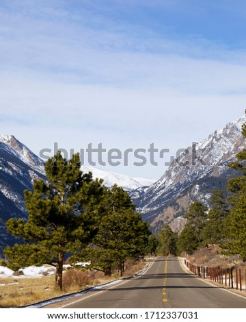 Entry roadway to the Rocky Mountain National Park in Estes Park, Colorado.  Trees, meadows and tall mountains on view along this roadway in Colorado allow tourists access to nature.   #1712337031
