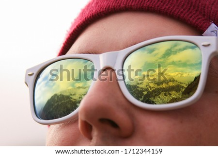 Mountains reflected in sunglasses of the traveler. Active person looking at mountains in winter. Image can be used for winter sport, outside in nature.