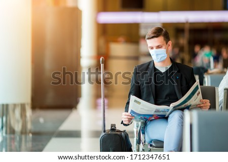 Man wearing a mask for prevent virus in international airport lounge waiting for flight aircraft. Protection against Coronavirus and gripp #1712347651