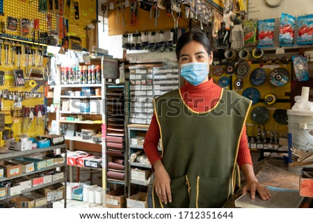 Entrepreneur woman in his business working with face masks during quarantine for the epidemic of disease caused by COVID-19. Royalty-Free Stock Photo #1712351644