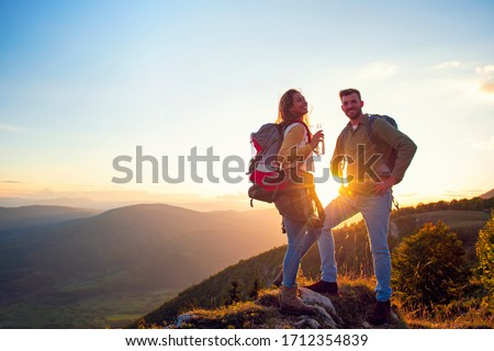 Young Couple Hiking On The Peak of Mountain drinking water Royalty-Free Stock Photo #1712354839