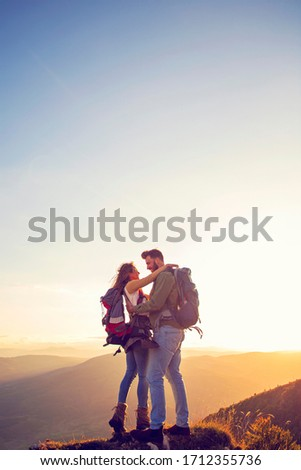 Hikers with backpacks relaxing on top of a mountain and enjoying the view of valley #1712355736