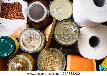 Close up of non-perishable food, canned goods and toilet paper. Overhead view.