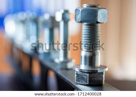 View of the bolts and nuts (fasteners). A bolt is a form of threaded fastener with an external male thread. Bolts are very closely related to screws. Bolts are often used to make a bolted joint. Royalty-Free Stock Photo #1712400028