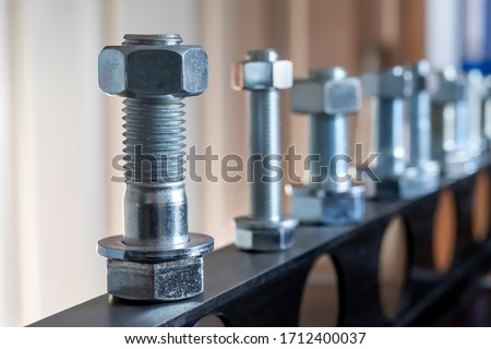 View of the bolt, nut and washer (fasteners). Bolts are for the assembly of two unthreaded components, with the aid of a nut. Screws in contrast are used in components which contain their own thread. #1712400037