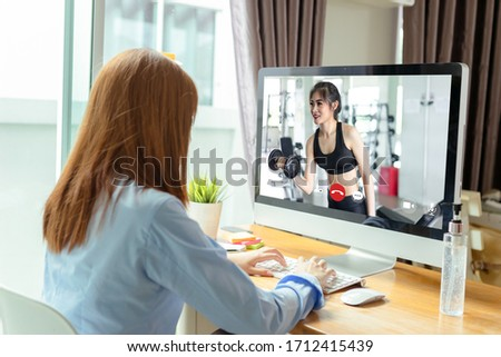 Video call user interface of young asian woman learning and studying with online personal trainer in fitness gym doing practice exercise when quarantine staying at home, self isolation concept. #1712415439