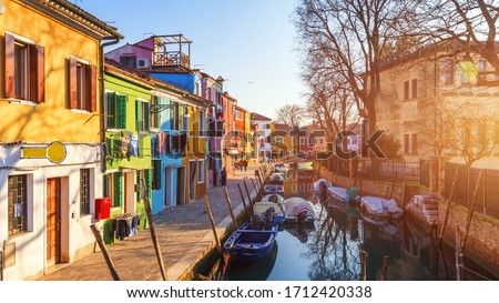 Street with colorful buildings in Burano island, Venice, Italy. Architecture and landmarks of Burano, Venice postcard. Scenic canal and colorful architecture in Burano island near Venice, Italy #1712420338