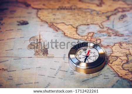 Old vintage retro golden compass on ancient map. Selective focus, shallow depth of field. Concept of world travel, sightseeing and tourism. Royalty-Free Stock Photo #1712422261