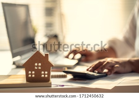 Hand of Business people calculating interest, taxes and profits to invest in real estate and home buying Royalty-Free Stock Photo #1712450632