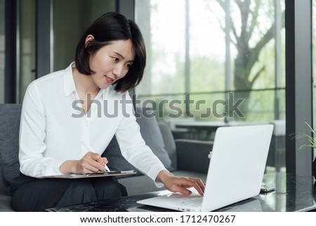 An Asian business woman with short hair is working #1712470267