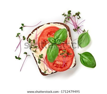 Open sandwich tomato, mozzarella, soft cheese, basil. Homemade vegan sandwich with rye bread, microgreen isolated on white, top view. Healthy eating, diet tomato sandwich closeup #1712479495