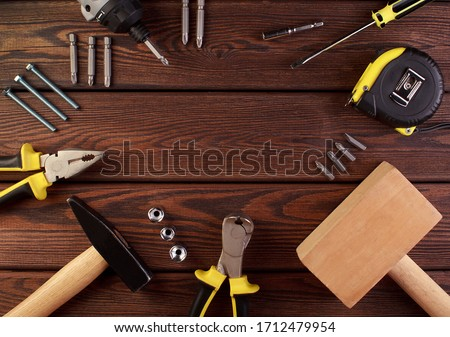 Tools worker, hammer, screwdriver, pliers on a wooden background, top view #1712479954
