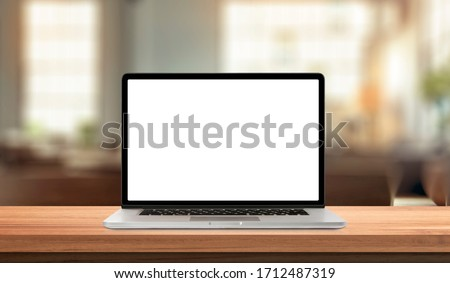 Laptop or notebook with blank screen on wood table in blurry background with house or office modern ,nature orange bokeh and sunlight in morning. Royalty-Free Stock Photo #1712487319