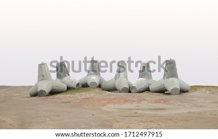 Concrete breakwaters folded in a row on the shore. Royalty-Free Stock Photo #1712497915