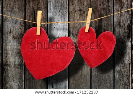 Red heart  hanging on clothesline on wood background. #171252239